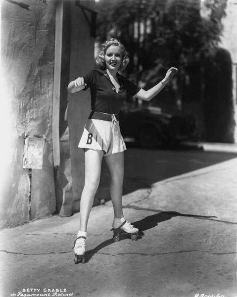 Betty Grable Posed with Arms Raised Up with Legs Spread in Black Short Sleeve Collar Shirt and White Skirt Premium Art Print