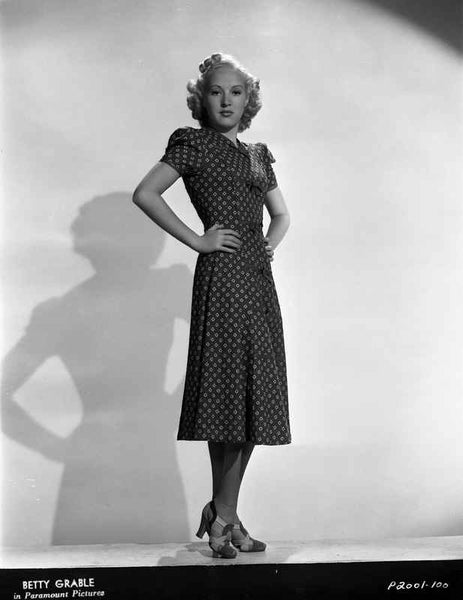 Betty Grable Posed with Hands Laid on the Waist in Black High Neck Polka Dot Dress and High Heel Sandals Premium Art Print