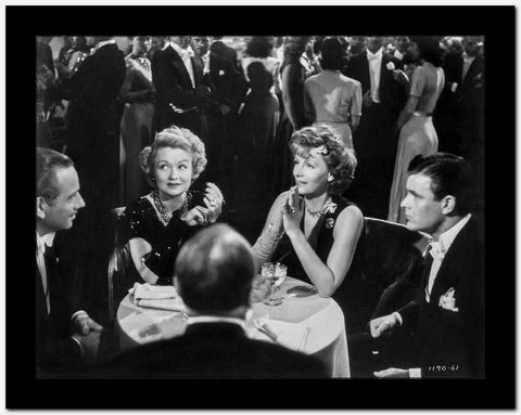 Greta Garbo Chatting with Friends on a Table High Quality Photo