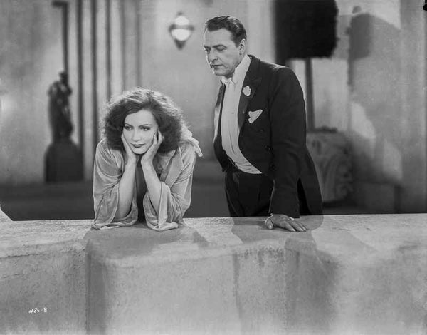 Greta Garbo Leaning while a Mans Talking Premium Art Print