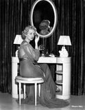 Bette Davis Seated on a Cushion Chair while Applying Make-Up on the Face in Black Sheer Long Sleeve Dress Premium Art Print