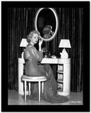 Bette Davis Seated on a Cushion Chair while Applying Make-Up on the Face in Black Sheer Long Sleeve Dress High Quality Photo