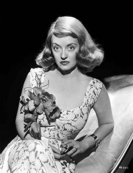 Bette Davis Leaning Back on a White Reclining Chair with Hands Together in White Floral Dress Premium Art Print
