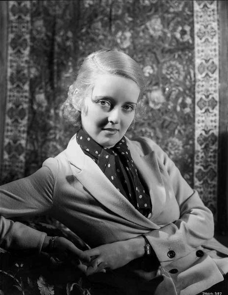 Bette Davis Leaning Back on the Chair in Black Polka Dot Neckerchief and White Suit Dress Premium Art Print