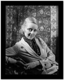 Bette Davis Leaning Back on the Chair in Black Polka Dot Neckerchief and White Suit Dress High Quality Photo