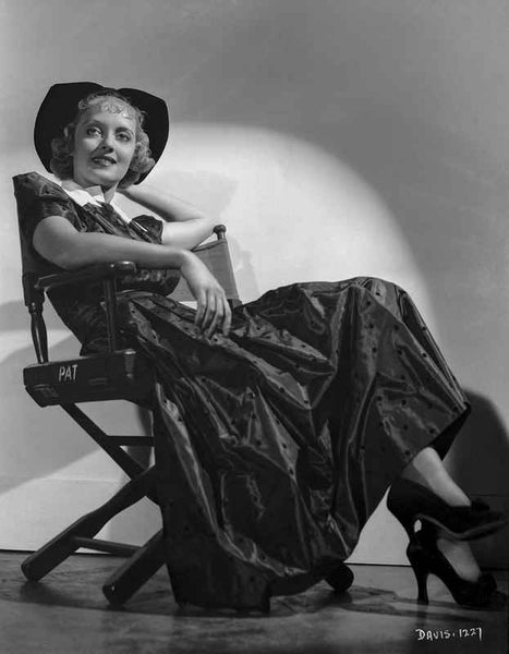 Bette Davis Seated on a Director's Chair in Black Hat and Black Dress with White Collar Premium Art Print