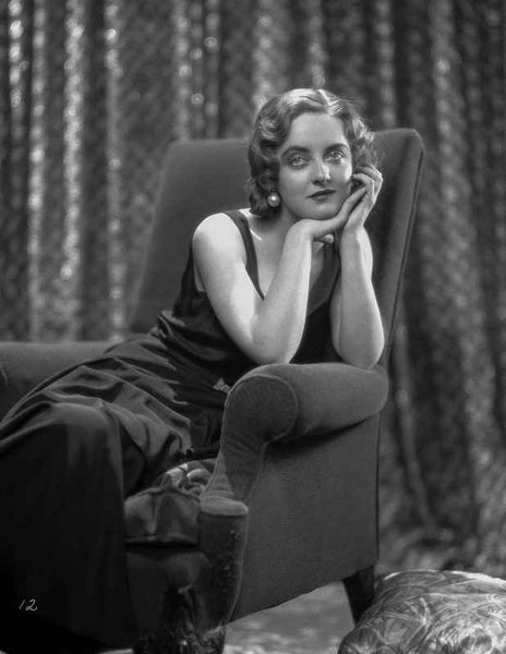 Bette Davis Seated on a Black Couch with Chin Leaning on Hand in Black Velvet Dress with Marcel Wave Hair Premium Art Print