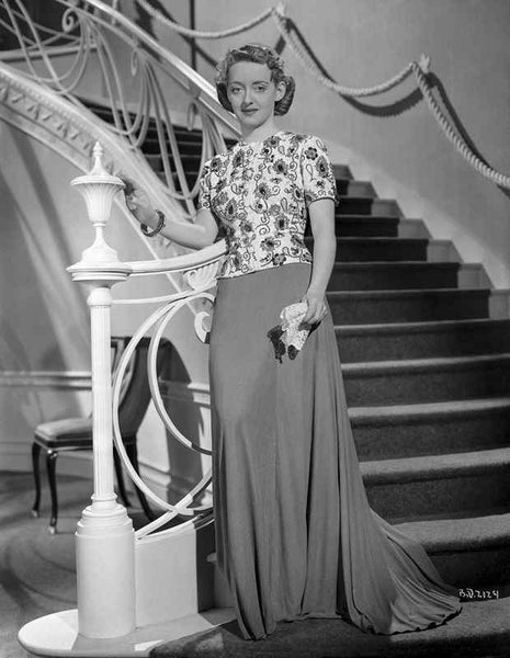 Bette Davis standing Beside on a White Staircase Metal Railing and Holding a Handkerchief in Floral Short Sleeve Shirt and Long Skirt Premium Art Print