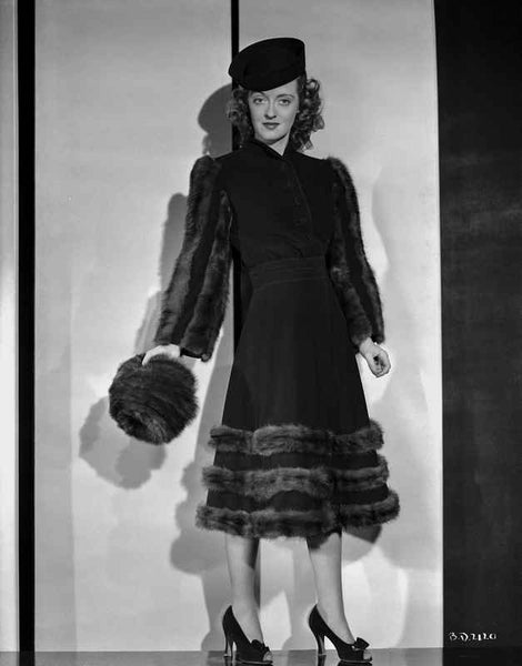Bette Davis Posed Holding a Fur Hat in Black Dress with Layered Fur Bottom and Black Cap Premium Art Print