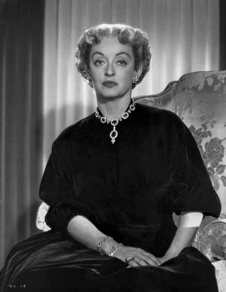 Bette Davis Seated on a Couch with Hands Together Laid on the Lap in Black Silk Dress and Gem Necklace with Marcel Wave Hair Premium Art Print
