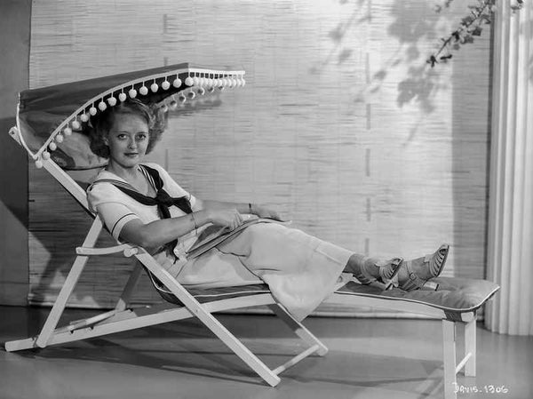Bette Davis Seated on a Reclining Chair with Hands on the Lap in White Sailor Suite and Tied Black Scarf Premium Art Print