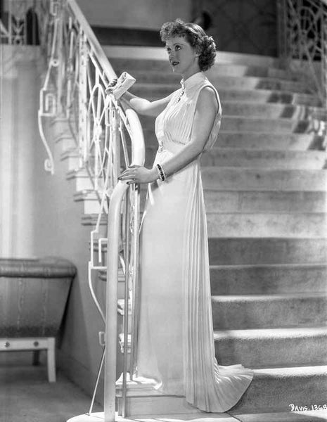 Bette Davis Posed Holding on the Staircase Railing in White Sleeveless Chiffon Long Dress Premium Art Print