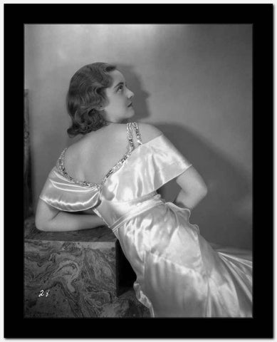 Bette Davis Leaning Back on the Table Facing Back and Looking Up in White Silk Dress High Quality Photo