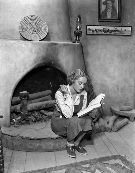 Bette Davis Seated Near the Fireplace with Cigarette on Hand while Reading a Book in White Long Sleeve and Apron Dress Premium Art Print