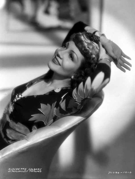 Claudette Colbert sitting in Floral Dress with Two Hands on Head Premium Art Print