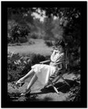 Claudette Colbert sitting on Chair, wearing White Dress High Quality Photo