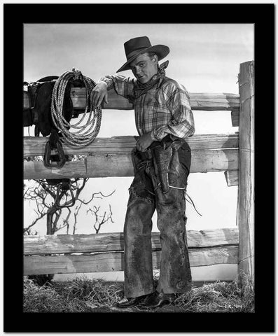 James Cagney Posed Facing to the Right in Checkered Long Sleeve Shirt and Cowboy Hat while Leaning on the Wood Fence with Left Hand on the Belt High Quality Photo