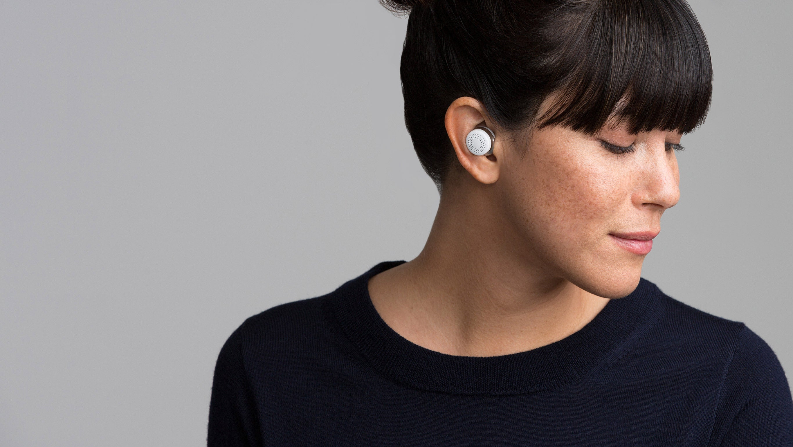 Woman smiling and using Here One earbuds