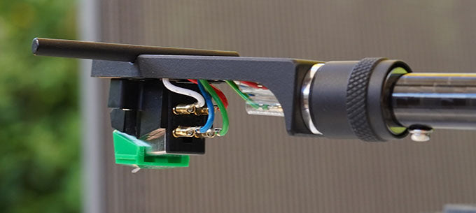 The cartridge mounted on tonearm showing wires at back