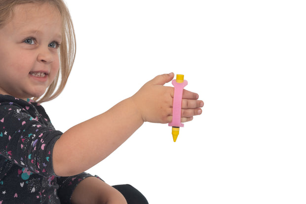 Little girl with grip issues hold a crayon adapted with a pink eazyhold silicone cuff