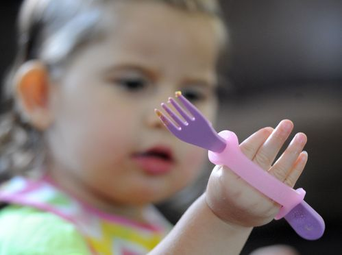 Girl with weak grip holding a fork with help from an eazyhold eating aid.