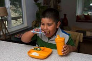 Child gripping a special needs blue silicone eating utensil.