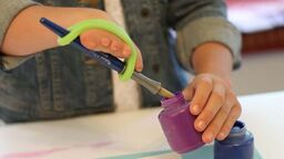 Child dipping an eazyhold adpted paintbrush into paint with a green silicone cuff.