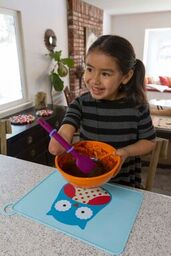 Girl with a limb loss disability stirring a bowl of cake batter with an adapted spoon.