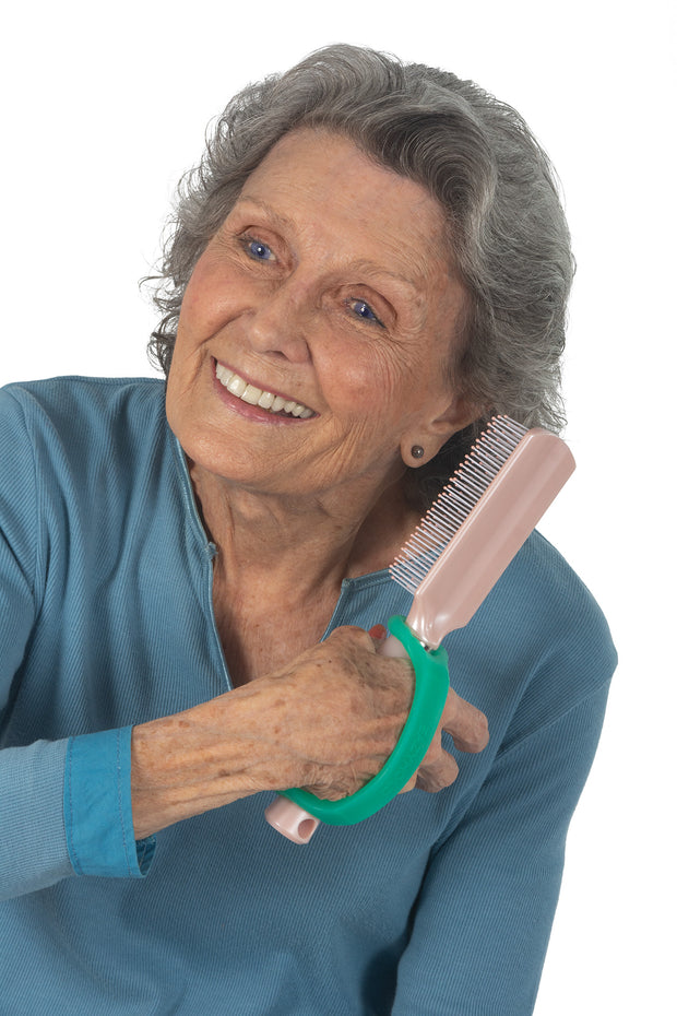 Disabled woman with stroke holds an adapted hairbrush with a U Cuff.