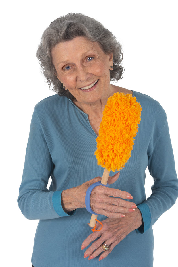 Woman with reduced grip holding a duster with the help of an ADL assistive device
