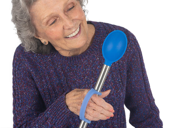 Woman with arthritis hold kitchen implement adapted with a blue eazyhold grip assist