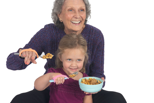 Mom and child with grip disabilities using pink eazyhold spoon adapters.