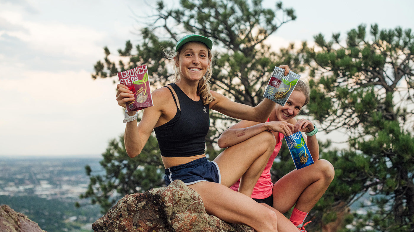 Two women holding bags of Crunchsters while out on a hike