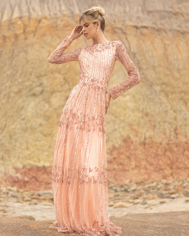 Primavera Couture 3685 This long beaded evening gown has a bateau neckline and long embellished sleeves.  The A line design is beaded to the floor and has a boho tone. Available colors:  Champagne, Black Multi  Available sizes:  0-24