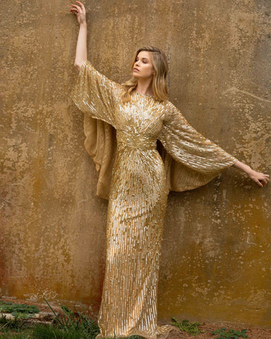 Primavera Couture 3687 This is a sequin beaded long evening gown with cape sleeves that wrap around the arms and flow off the back in a cape.  It is long and fitted to the floor with bateau neckline. Available colors:  Gold, Pewter  Available sizes:  0-24