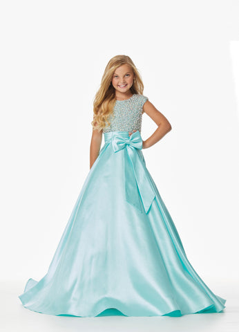 Ashley Lauren 8019 This little girl pageant ballgown has a beaded and pearl bodice and accent bow at the waistline.  This Little Girl and Tween Pageant Dress has a high neckline and high back with cap sleeves. It completes with an A line skirt with a train.  Colors  Aqua, Lilac  Sizes  4, 8, 10, 12, 14