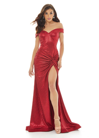 Ashley Lauren 11006 This metallic jersey off the shoulder evening gown is perfect for your next Prom or Pageant. The hip is accentuated with a twist knot detail that gives way to a high left leg slit. The skirt is finished with horsehair.   Colors Gunmetal, Red  Sizes 0, 2, 4, 6, 8, 10, 12, 14, 16    Off Shoulder Twist Knot Detail Criss Cross Back Fitted Skirt Metallic Jersey Prom Dress