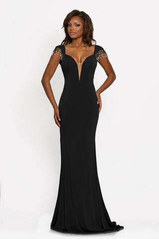 Johnathan Kayne 2275 This is a fitted long evening pageant gown with a plunging neckline and flared long skirt.  The neckline on this prom dress is plunging with a mesh panel and features fringe embellished cap sleeves that lead to an open mid v back. Colors  Black, Red  Sizes  00, 0, 2, 4, 6, 8, 10, 12, 14, 16