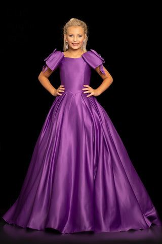 Sugar Kayne C110 by Johnathan Kayne is a Long Duchess Sating Girls Pageant Gown. This Dress Features Large Crystal accented Double Bows along the shoulders with spaghetti straps. Pleated A Line Skirt that will flow on stage!  Available Colors: Purple, Red, Soft White  Available Size: 2-16