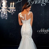 Adagio Bridal D9145 This romantic sheer neckline floral lace applique mermaid wedding dress features sheer back and bridal buttons down the elongated back and a mermaid tulle skirt with a train.   Destination Bridal Gown Wedding Dress   Available sizes:  00, 0, 2, 4, 6, 8, 10, 12, 14, 16, 18, 20, 22, 24, 26, 28, 30  Available colors:  Ivory, White