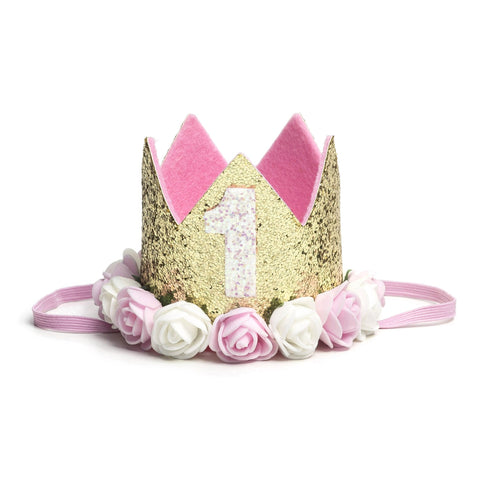 Sweet Wink -  The Gold Blush #1 Flower Crown is the perfect addition to any first birthday! This fun and festive flower crown makes a great birthday present or is an adorable way to dress up your little one for a cake smash, birthday party, or Instagram photo. Item description:  Gold glitter crown White glitter #1 Pink and ivory flowers trim the base of the crown Light pink felt lining inside the crown and on the bottom of the crown to ensure comfort and softness on the child's head Light pink elastic to se