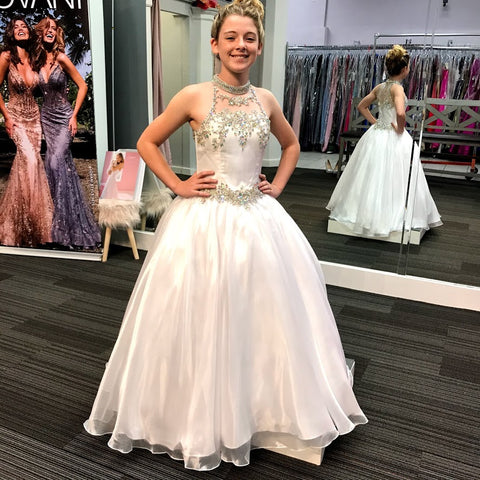Little Rosie LR2303 is a long Glitz Girls Pageant Dress. Featuring a sheer Illusion high neckline fully embellished with a Crystal ab Choker. Open Back with 4 Rows of AB Crystal Rhinestone embellished straps. Embellished bodice and waistband. Lush Ballgown straight skirt.