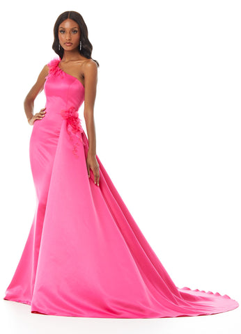 Ashley Lauren 11003 This one shoulder gown with floral applique is perfect for your next event. The shoulder strap and hip are adorned with romantic floral applique. The asymmetrical overskirt flows perfectly on top of the fitted skirt.  Colors Fuchsia, Black/White  Sizes 0, 2, 4, 6, 8, 10, 12, 14, 16  One Shoulder Floral Applique Overskirt Satin