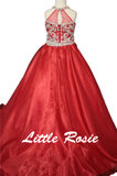 Little Rosie LR2662-1 Stunning 3 piece Girls Pageant Wear Set. Two piece Romper shorts with high neckline crystal rhinestone embellished with beaded tassels on the top and embellished hem on the shorts. Detachable Lush overskirt with front opening.  The dress itself can be worn in two different ways as a romper with beaded shorts and also with a sheer organza floor length skirt that is detachable.  FEATURES:  Fabric Type:  Satin / Organza Neckline: Halter Hidden Zipper Closure Available Size: 8 Available Co