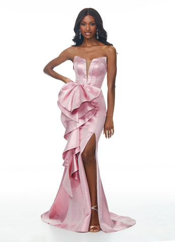 Ashley Lauren 1699 sweetheart neckline with ruffle down one side and high side slit down the other side of the skirt.  Its fabric is metallic brocade shimmer.  prom dress pageant gown evening gown, red carpet gown   Available colors:  Fuchsia, Royal, Blush  Available sizes: 0, 2, 4, 6, 8, 10, 12, 14, 16  Be a true queen in this stunning metallic brocade gown. We are in love the dramatic ruffle details and high slit.  Metallic Brocade Strapless V-Neckline Slit Ruffle Details