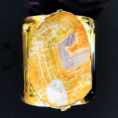 Gold plated cuff with gold edged orange stone