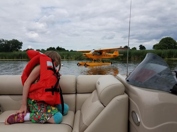 girl wearing life jacket looks at seaplane from boat
