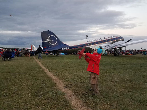 child with toy airplane in front of dc airplane