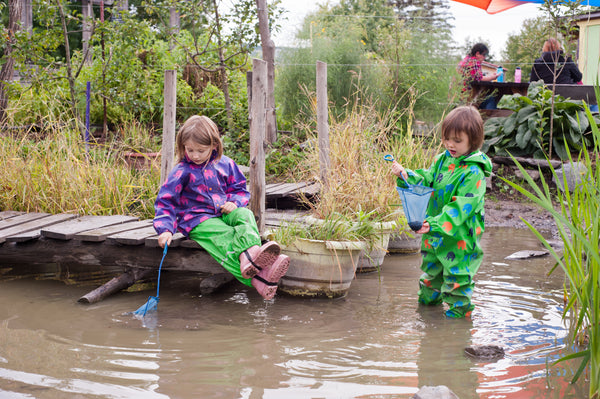 Biddle and Bop kids sitting in pond at Ithaca Children's Garden in Biddle and Bop waterproof gear