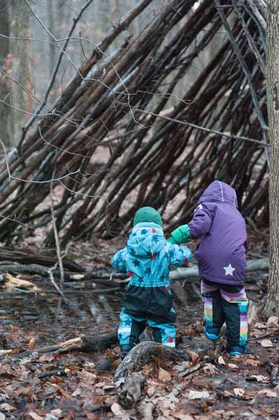 two kids in the woods at a wood teepee in waterproof winter gear from biddleandbop